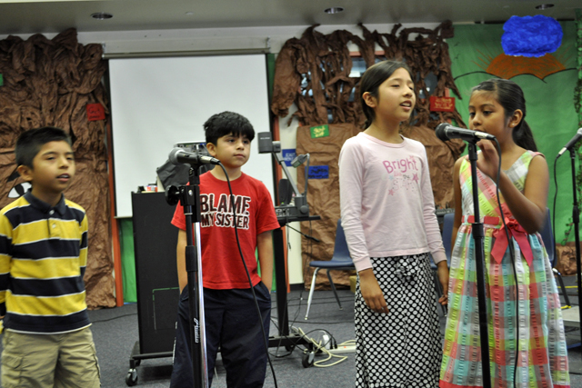 Noe Lopez, 7, Edward Gonzalez, 8, Sarahy Lopez, 9, and Jane Sandoval, 8, perform as Baby Bear, Papa Bear, Goldilocks and Mama Bear, respectively, during a rehearsal at Garfield Elementary's summer arts program. The program is part of a first-ever effort by Santa Ana Unified to let teachers design summer school classes. The performing arts program allowed students to sing, act, design sets, create costumes and market a production. Behind them are sets designed by students in the class.