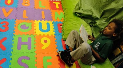 A 4th grader finds a quiet place to read during breakout groups in Lora Johnson's class at George Cox Elementary School in Gretna, La. In Louisiana, teacher preparation programs are now judged partly on the test scores their graduates' students earn — part of a growing national movement to assess education schools based on their results. (Photo by Ted Jackson, Nola.com / The Times-Picayune)