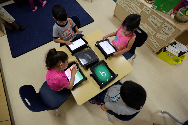 In this April 2, 2014 file photo, Pre-K students use electronic tablets at the South Education Center in San Antonio.