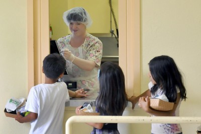 Cafeteria worker Sophia Villareal gets student's names as kids get their at Brockton Elementary School Monday, June 29, 2012 in Los Angeles, Calif. (Photo by Richard Hartog/California Watch)
