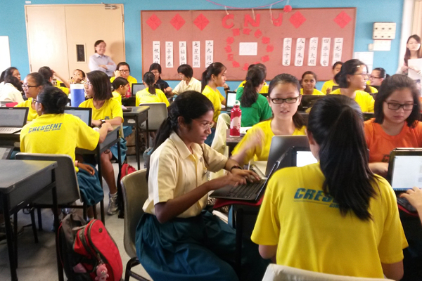 Students at Crescent Girls School in Singapore discuss conflict and discrimination in groups while working on a shared Google Doc. (Photo: Sarah Butrymowicz)