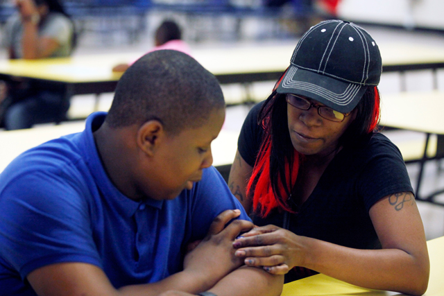 At Quitman's back-to-school night, D'Andre shows his mother, Taneka, a mood ring he got on a trip to Great Adventure. (Amanda Brown / NJ Spotlight)