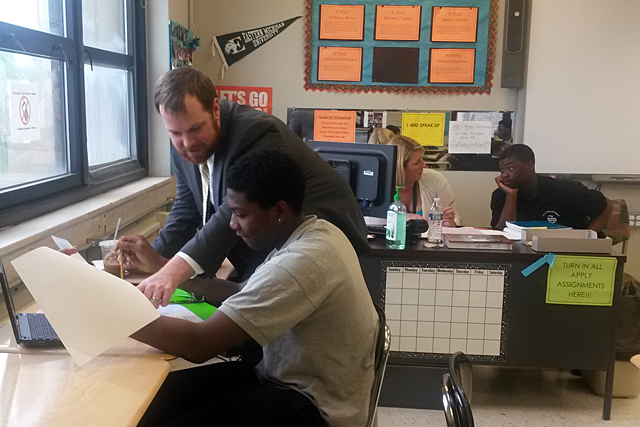 Jeff Maxwell, former principal of Detroit's Southeastern High School of Technology and Law, stops by a U.S. History course and checks in on student work. (Photo: Sarah Butrymowicz)