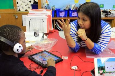 Kindergarten teacher Patty Lee helps a student with a math game on an iPad she got through DonorsChoose.org (Photo: Aisha Asif)