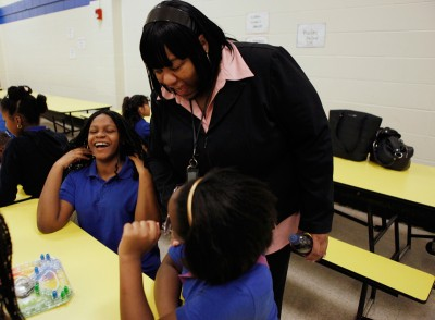 Charlette Givens supervises students Ashley McGee (left) and Déja Harper as they play a game in the cafeteria. (Photo by Amanda Eagen Brown)