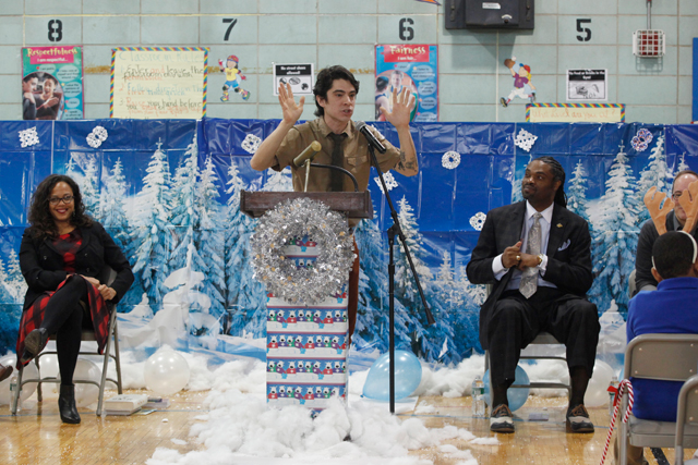 In December, Quitman staff turned the gym into a winter wonderland for an event to promote reading. Here, Principal Erskine Glover watches a speech by children's book author Kevin Sherry. (Amanda Brown / NJ Spotlight)