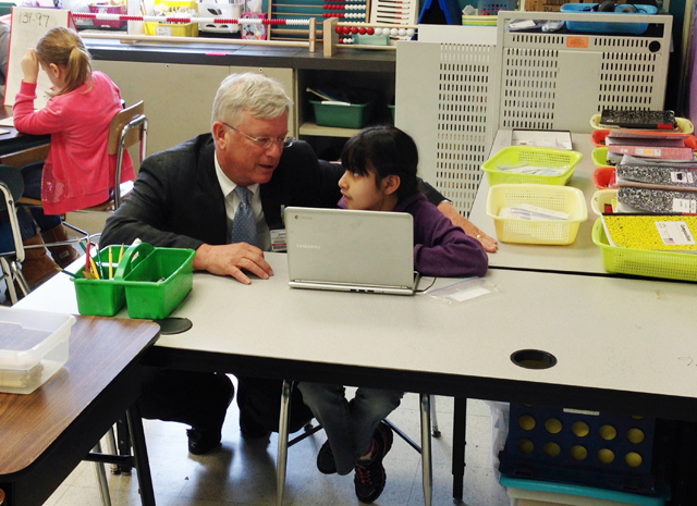 Superintendent Ken Eastwood asks second-grader Jocelyn Varela about her work on a digital lesson, which is part of the new blended learning program in New York's Middletown Enlarged City School District. (Photo: Meghan E. Murphy)