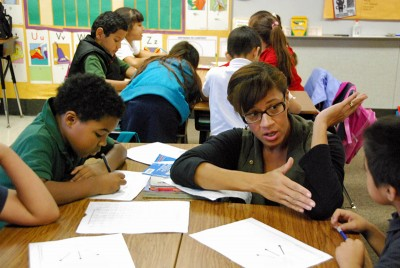 Writing coach Jandella Faulkner helps students at Edison Elementary use Thinking Maps to tell a story. (Photo by Stephen Smith)