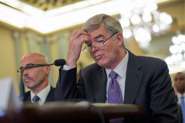 In this July 9, 2014, file photo, NCAA President Mark Emmert scratches his forehead as he testifies on Capitol Hill in Washington before the Senate Commerce, Science and Transportation hearing on the NCAA's treatment of athletes. At left is Dr. Richard M. Southall, Associate Professor, Department of Sport and Entertainment Management. (AP Photo/Pablo Martinez Monsivais, File)