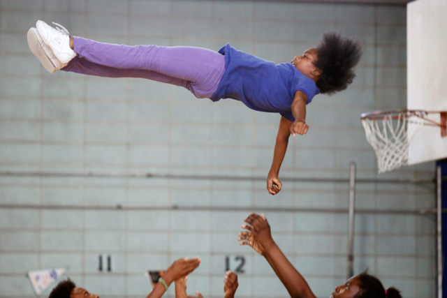 Nydresha's cheerleading teammates hoist her into the air for one of the seven stunts they would perform in a routine for a citywide tournament. (Amanda Brown / NJ Spotlight)