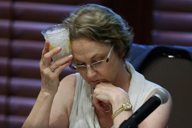 Oklahoma State Board of Education member Cathryn Franks holds a glass with ice to her head during a board meeting in Oklahoma City, Wednesday, July 23, 2014. The board has again voted to delay a formal plan for adopting new education standards in math and English amid opposition to the proposal by three education groups that represent public school boards and administrators from across Oklahoma. (AP Photo)