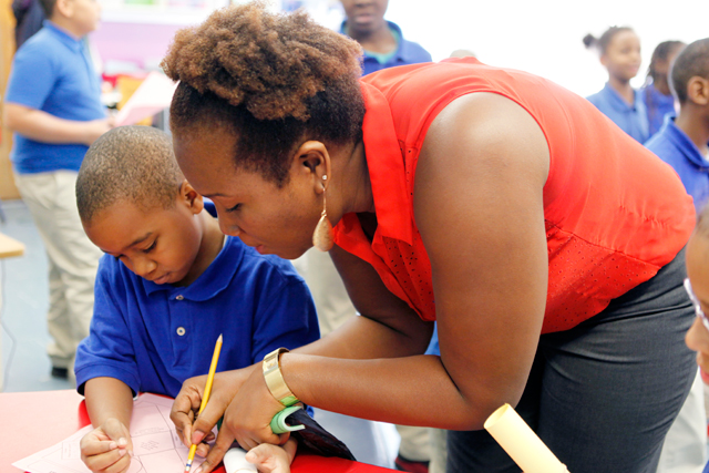 Quitman third-grade teacher Elizabeth Rooks works with a student on a project during a day of special activities to celebrate improved test scores. (Amanda Brown / NJ Spotlight)