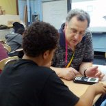 Teacher Howard A. Stern works with a student who is programming a graphing calculator to perform a simple math game. (Photo: Nichole Dobo)