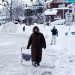 A woman walks along a snow-covered street in the south Buffalo area on Thursday, Nov. 20, 2014, in Buffalo, N.Y. A new blast of lake-effect snow pounded Buffalo for a third day piling more misery on a city already buried by an epic, deadly snowfall that could leave some areas with nearly 8 feet of snow on the ground when it's all done. (AP Photo/Mike Groll)