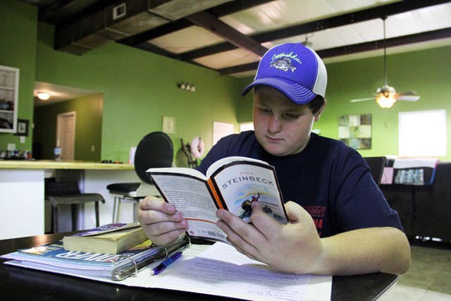 "Cody Beck reads a book that was assigned by his teacher at Grenada Middle School. Since April, Cody has been on a ""homebound"" program due to behavior, where he does his work at home and meets with a teacher for four hours each week for instruction. (Photo by Jackie Mader)"
