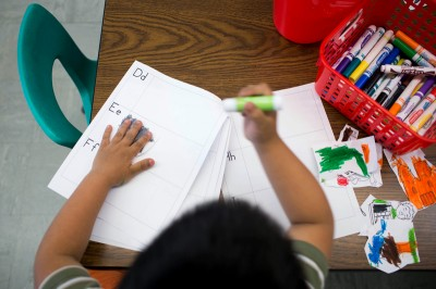 Students in kindergarten teacher Pang Moua's class glue pictures into ABC books Wednesday, June 5, 2013 at Little Canada Elementary School. (Photo by Jennifer Simonson/MPR)