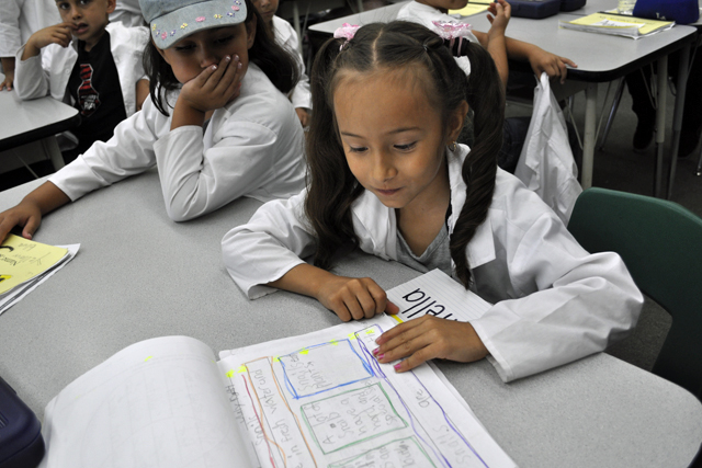 Estrella Magana, 6, clad in her lab coat, shows her lab book from a summer science class at Heninger Elementary in Santa Ana Unified. Estrella learned about snails, worms and pill bugs during the class, which included a museum field trip.
