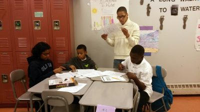 Students at Thurgood Marshall Academy work with one of their after-school helpers to figure out a science project. (Photo: Sarah Butrymowicz)